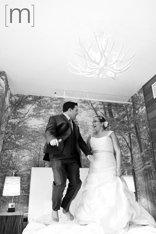 a photo of a couple jumping on the bed at a wedding at the gladstone hotel toronto