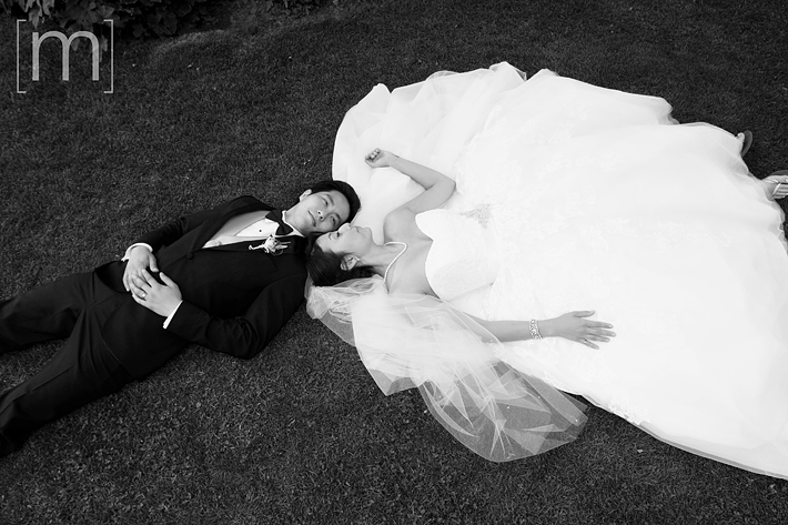 a photo of the couple laying down at a wedding at toronto music garden