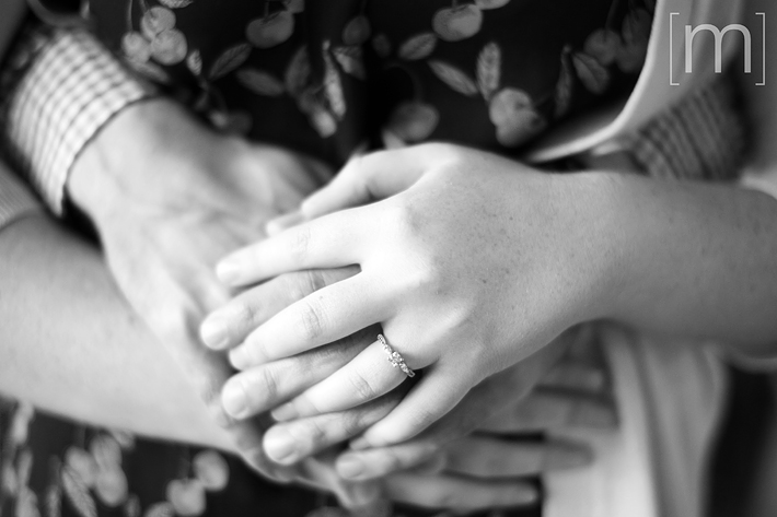 a photo of a couple holding hands with their ring at an engagement shoot in brighton ontario