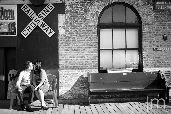 a photo of a couple kissing at a railway station at an engagement shoot in brighton ontari