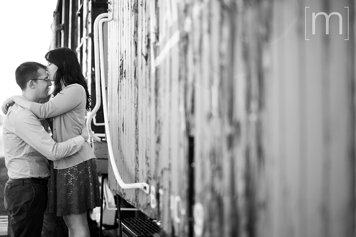a photo of a couple kissing on an old train at an engagement shoot in brighton ontari