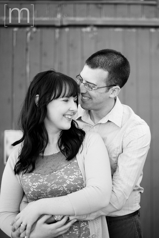 a photo of a couple laughing at an engagement shoot in brighton ontari