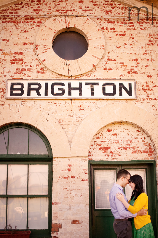 a photo of a couple snuggling against a building at an engagement shoot in brighton ontari