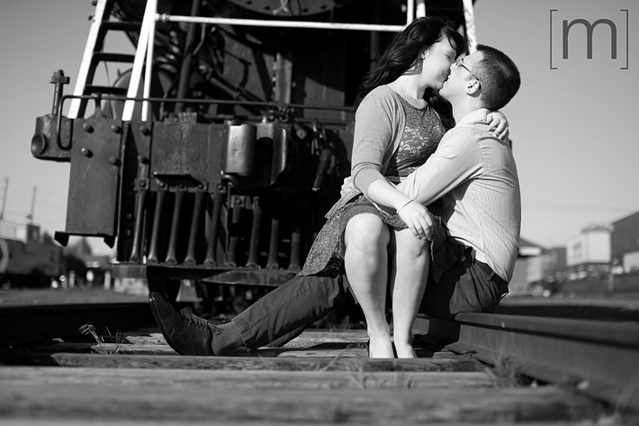 a photo of a couple snuggling on the train tracks at an engagement shoot in brighton ontari