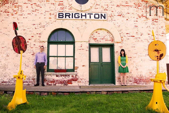 a photo of a couple standing against a building at an engagement shoot in brighton ontari