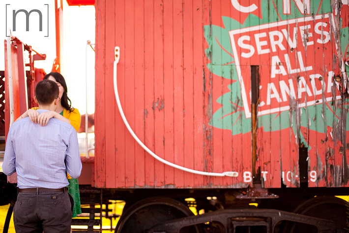 a photo of a cute couple against an old train at an engagement shoot in brighton ontario