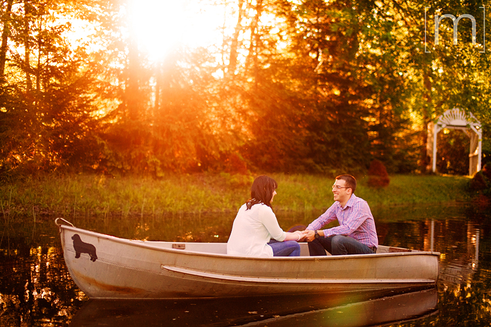 a photo of a cute couple sitting on a boat at sunset at an engagement shoot in brighton ontario
