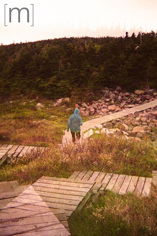 a travel photo of a person walking on a boardwalk in cape breton nova scotia