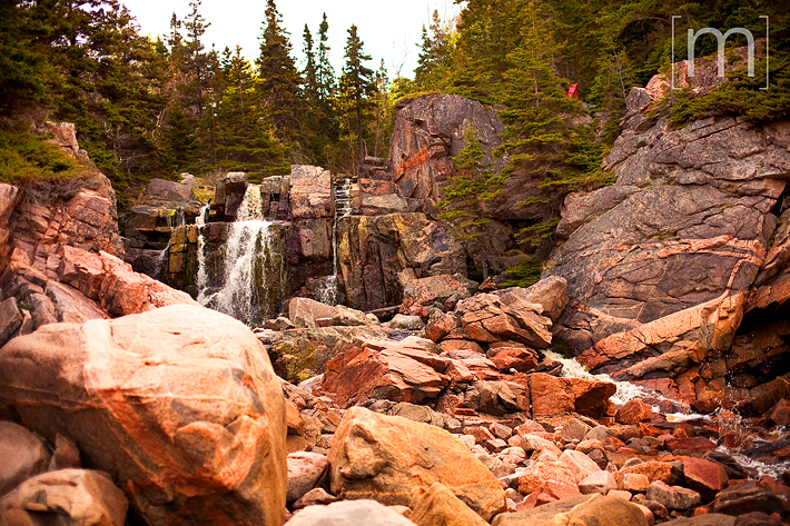 a travel photo of a rocky waterfall in cape breton nova scotia