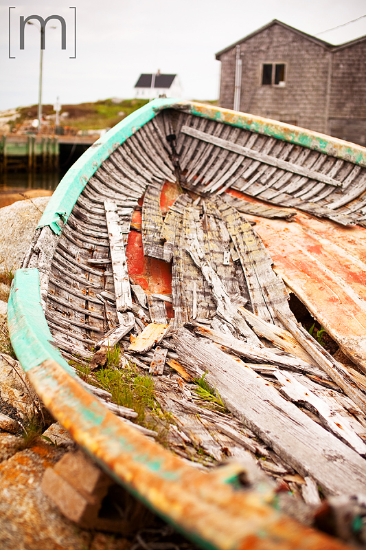 a travel photo of a rotting boat in peggys cove nova scotia