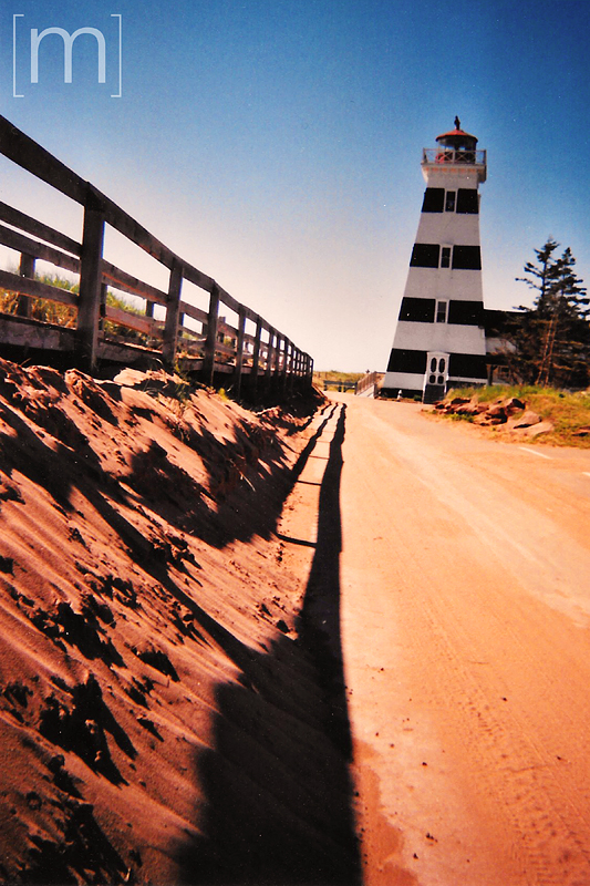 a travel photo of the red sands beach lighthouse in pei