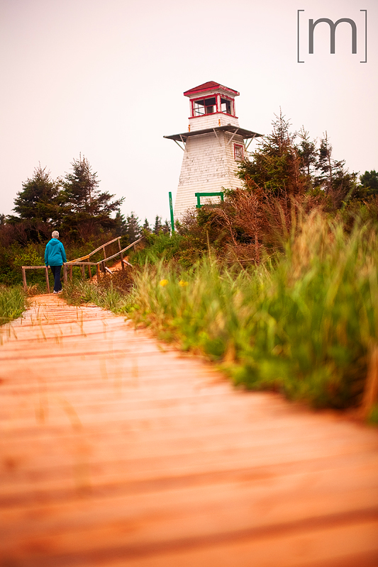 a travel photo of a sandy boardwalk lighthouse in pei