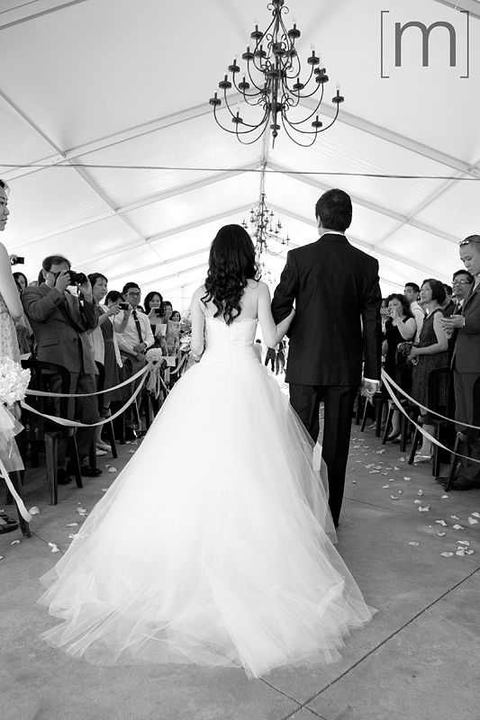 a photo of a bride being walked down the aisle at a wedding ceremony at angus glen golf club markham