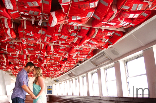 a photo of a couple cuddling under life jackets on a ferry at a spring engagement shoot on toronto island