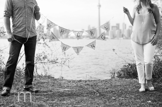 a photo of a couple holding a sign at a spring engagement shoot on toronto island