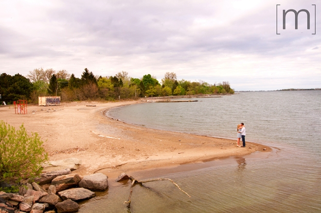 a photo of a couple kissing on a beach at a spring engagement shoot on toronto island