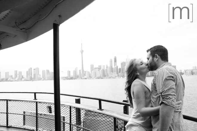 a photo of a couple kissing on a ferry at a spring engagement shoot on toronto island