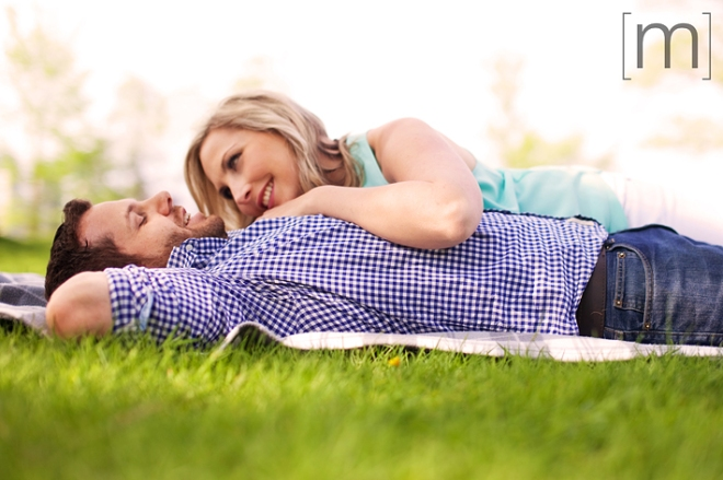 a photo of a couple laying down on the grass at a spring engagement shoot on toronto island