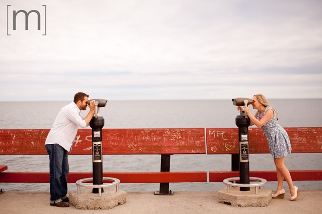 a photo of a couple looking at each other through binoculars at a spring engagement shoot on toronto island