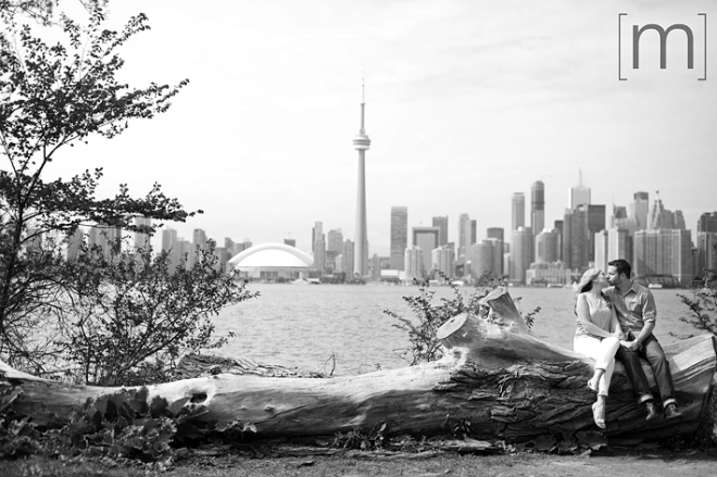 a photo of a couple sitting on a log with skyline at a spring engagement shoot on toronto island