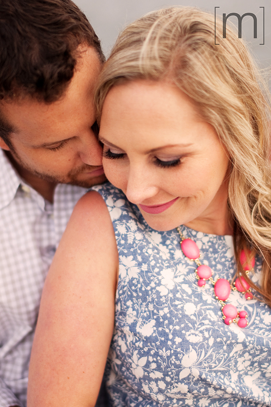 a photo of a couple snuggling at a spring engagement shoot on toronto island