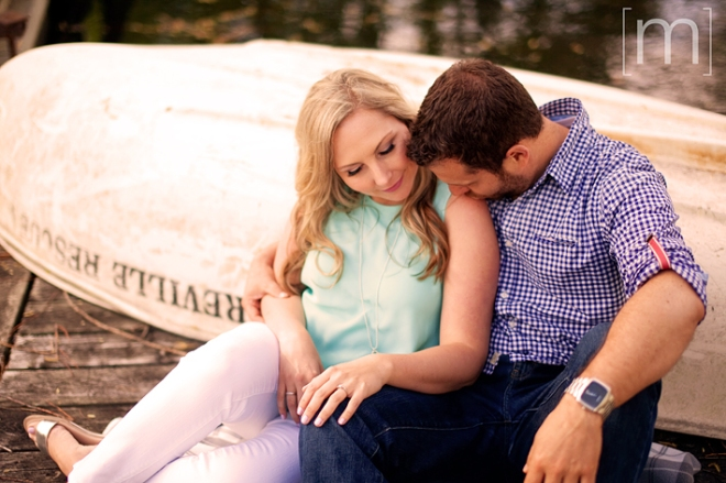 a photo of a couple snuggling against a boat at a spring engagement shoot on toronto island
