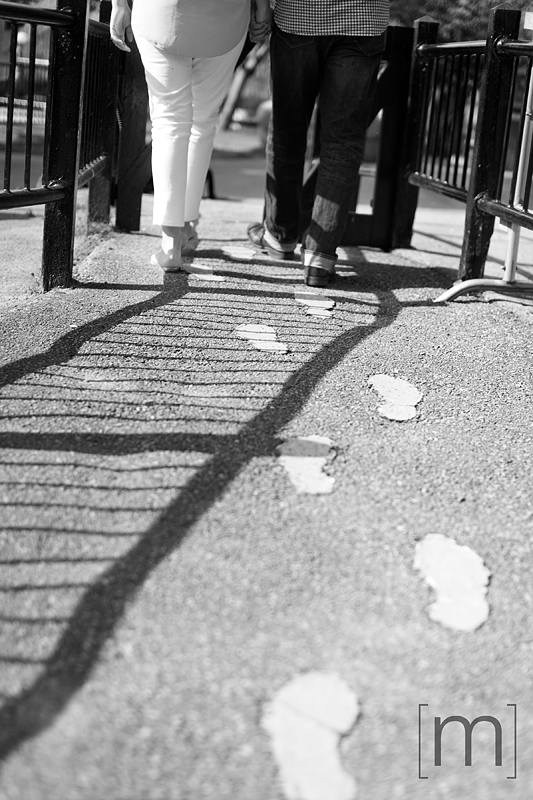 a photo of a couple walking with foot prints at a spring engagement shoot on toronto island