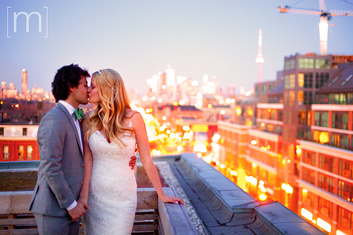 a photo of a couple kissing on the roof at sunset at a wedding at the gladstone hotel toronto