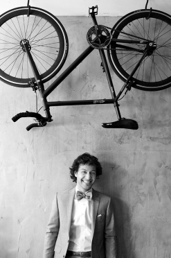 a photo of a groom with a bicycle over his head at a wedding at the gladstone hotel toronto