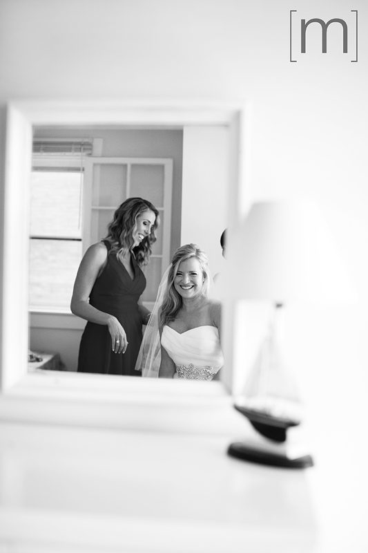 a photo of the bride laughing while looking in mirrior at a wedding at buffalo canoe club fort erie