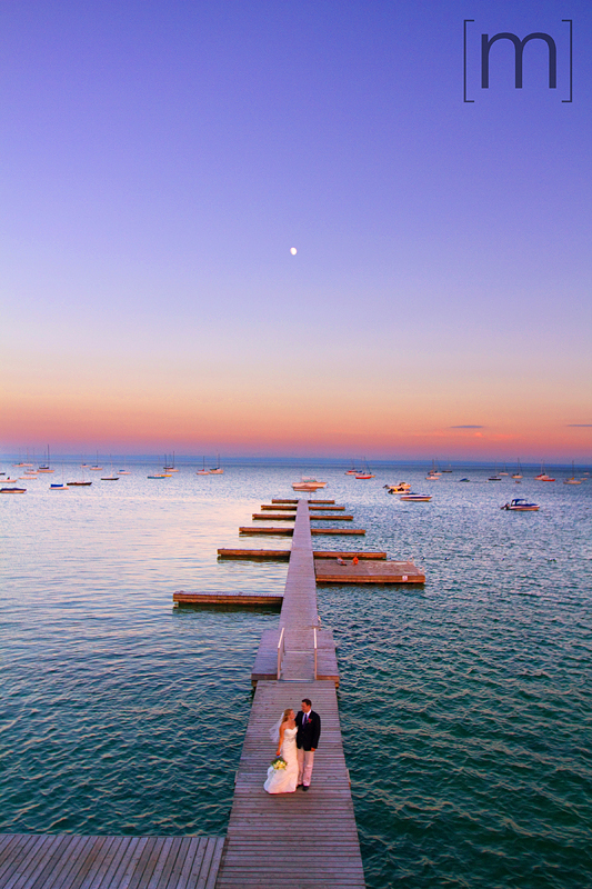 a photo of a couple on a pier at sunset with moon out at a wedding at buffalo canoe club fort erie