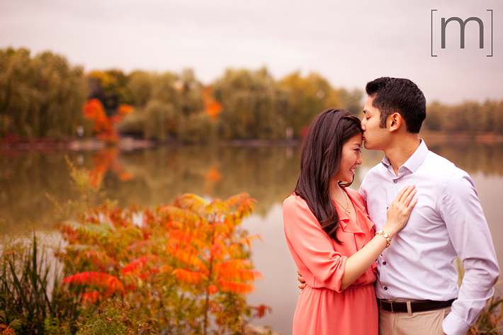 a photo of a couple cuddling in front of a pond at a fall engagement shoot at unionville markham
