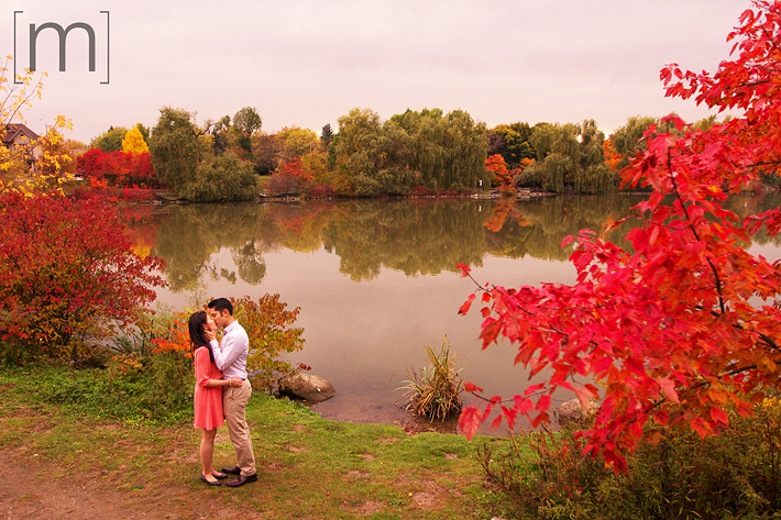 a photo of a couple kissing in front of a pond at a fall engagement shoot at unionville markham