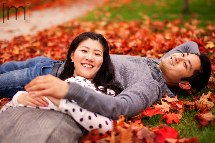 a photo of a couple kissing laying down with colourful leaves at a fall engagement shoot at unionville markham