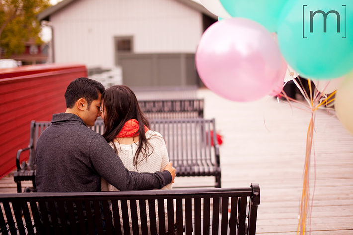 a photo of a couple cuddling with balloons at a fall engagement shoot at unionville markham