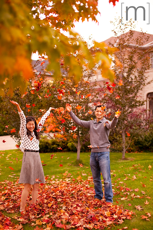 a photo of a couple throwing leaves at a fall engagement shoot at unionville markham