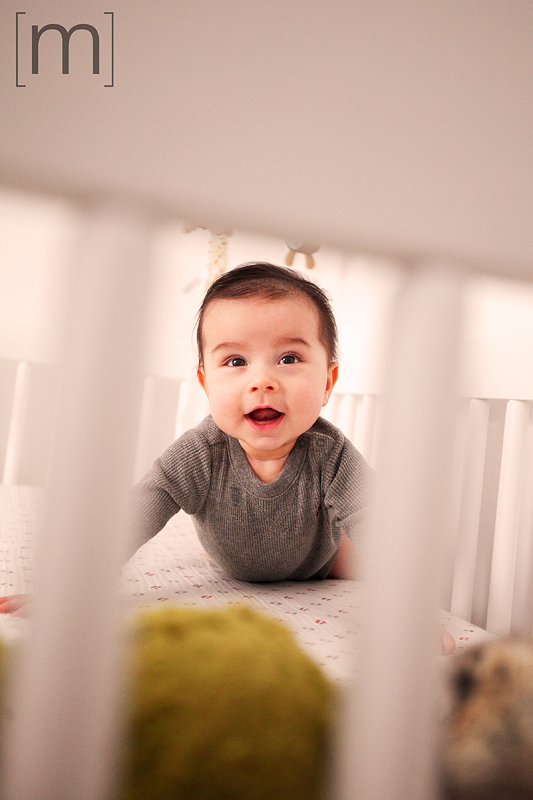 a family photo of a cute baby smiling in a crib in toronto
