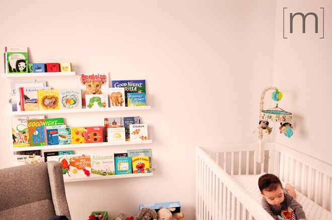 a family photo of a cute baby in a crib with books in toronto